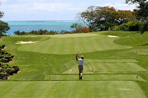 A golfer teeing off on a golf course overlooking the ocean.