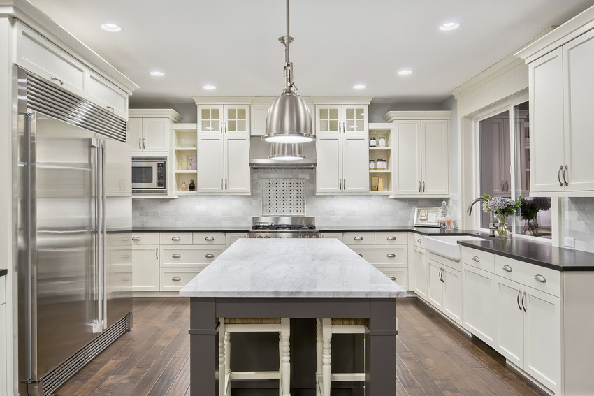 Luxurious kitchen with white marble countertop and chrome appliances.